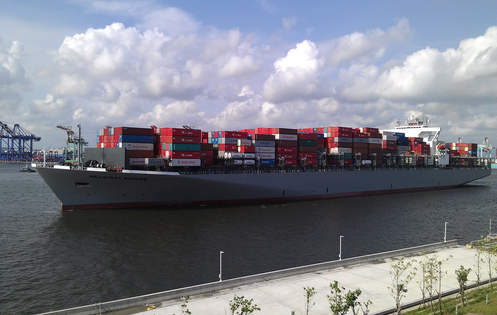 Massive freight ships exiting the port beside you